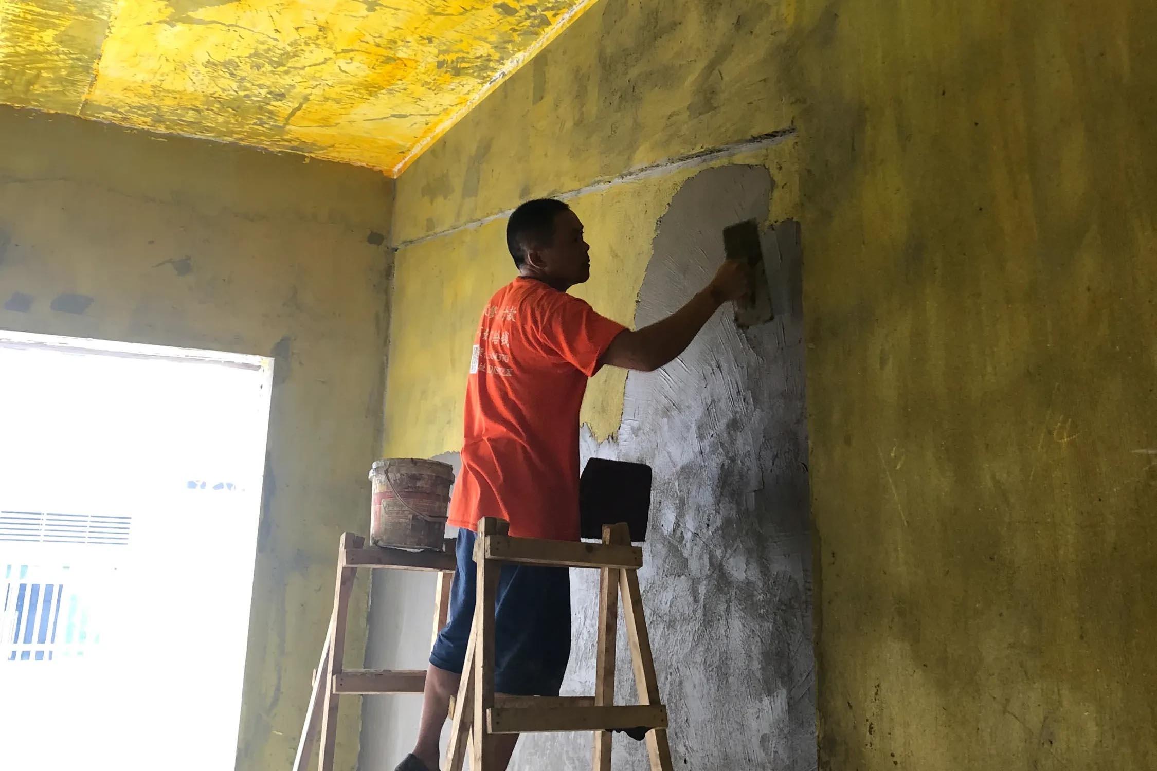 万科君望府,师傅正在对墙体不平处进行墙面抹平处理