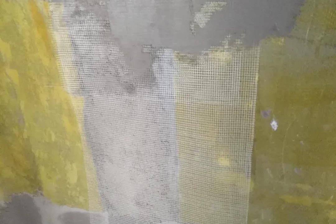中铁骑士府邸,正在为新抹的沙灰墙和老墙的交接处挂钢网